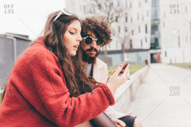 Young couple sitting outdoors, looking at smartphone