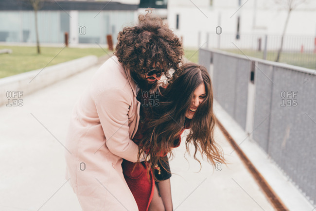 Young couple outdoors, fooling around, young man hugging young woman, laughing