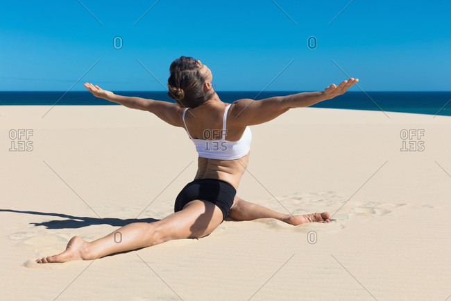 Rear view of woman on beach doing the splits, arms open in yoga position
