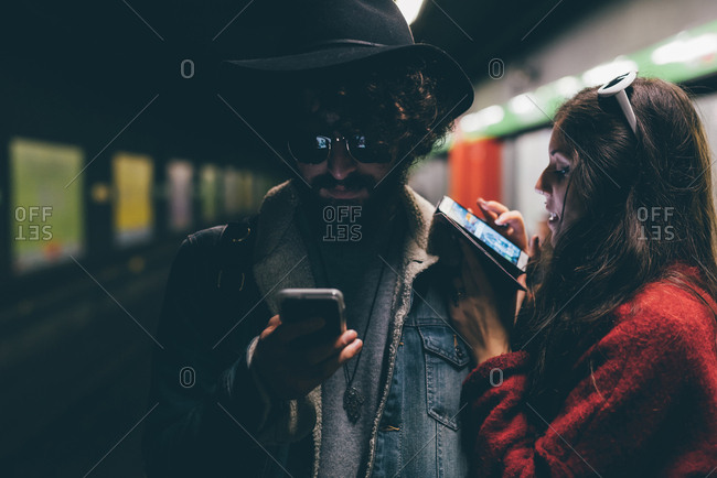 Young couple sitting on subway platform, looking at smartphones