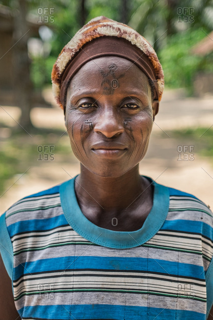 BENIN, AFRICA - AUGUST 31, 2017: Portrait of mature African woman with tattoos on face looking at camera