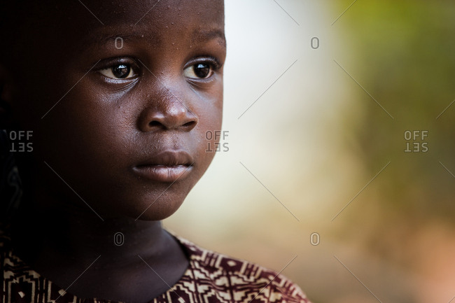BENIN, AFRICA - AUGUST 30, 2017: Horizontal outdoors portrait of adorable young African child looking away