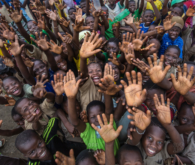 BENIN, AFRICA - AUGUST 30, 2017: Lots of smiling black children gesturing greeting with hands up and looking at camera