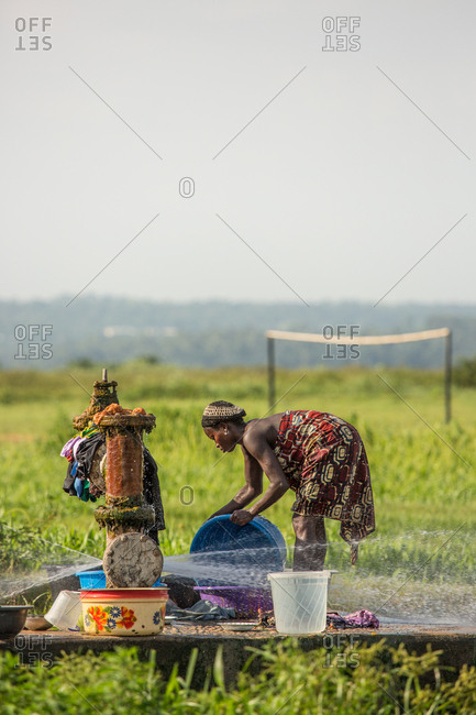 BENIN, AFRICA - AUGUST 31, 2017: Side view of black ethnic woman in file washing utensils at water point on background of tropics