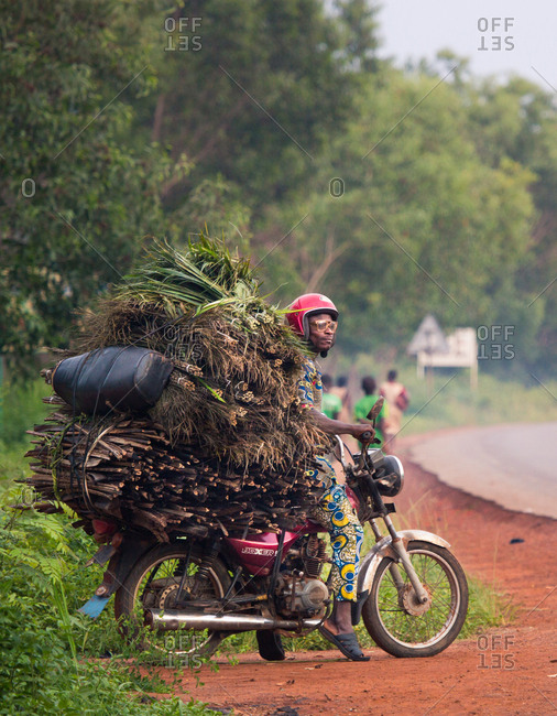 BENIN, AFRICA - AUGUST 31, 2017: Anonymous ethnic man sitting on motorcycle driving heaps of hay and twigs on tropical road background