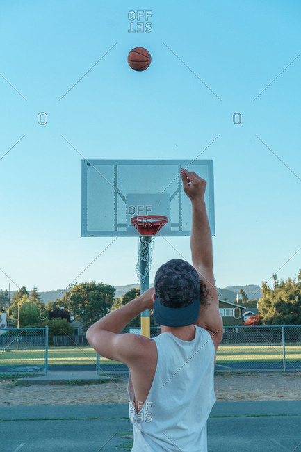 Sportsman in casual clothing and cap dribbling ball while playing basketball on sports ground