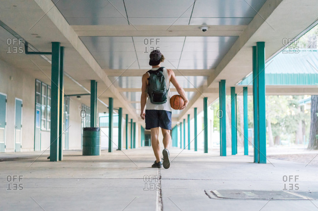 Back view of man in sportswear holding basketball and walking in gallery outside after workout