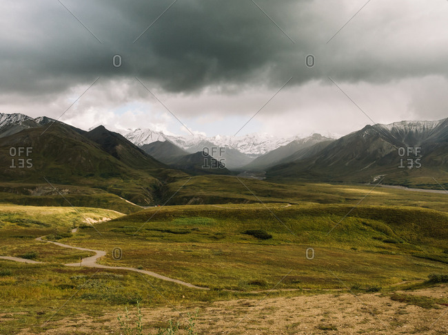Breathtaking view of spacious terrain on background of mountains ridge under gloomy sky