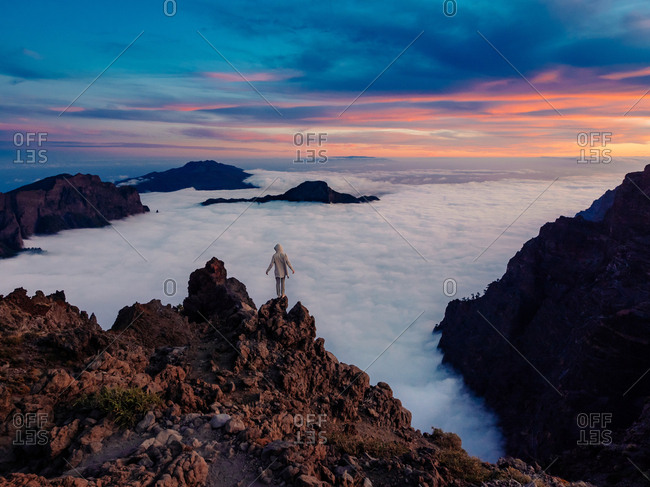 Traveler standing on rock with background of colorful sunset sky and mountains in fog