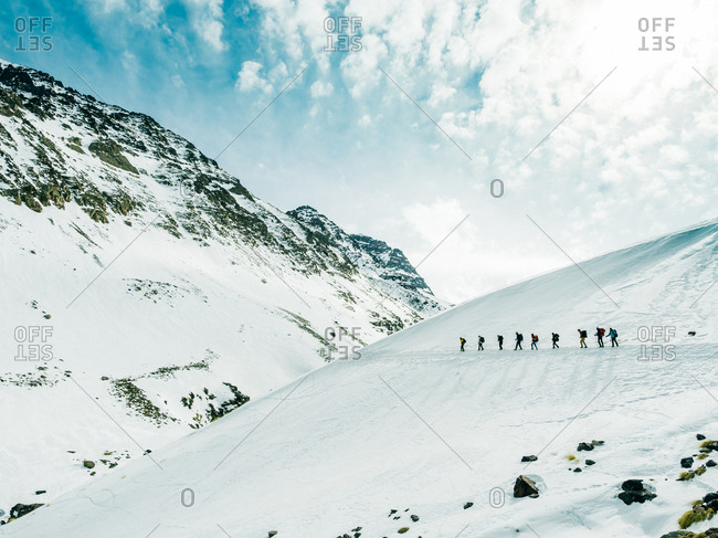 People walking on top of snowy mountains
