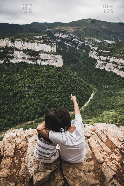 Unrecognizable man sitting on cliff, hugging his girlfriend and pointing at picturesque hills