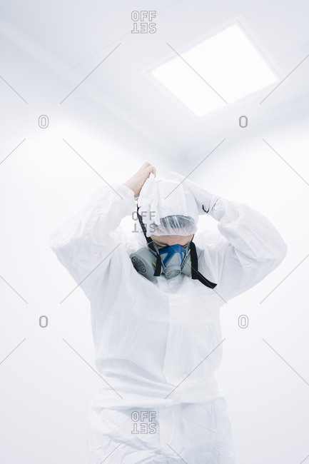 Scientist person preparing to work and putting on protective mask in laboratory