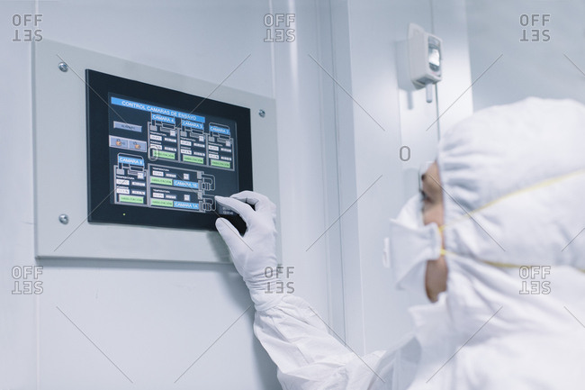 Side view of scientist providing research and operating with tablet on wall of laboratory