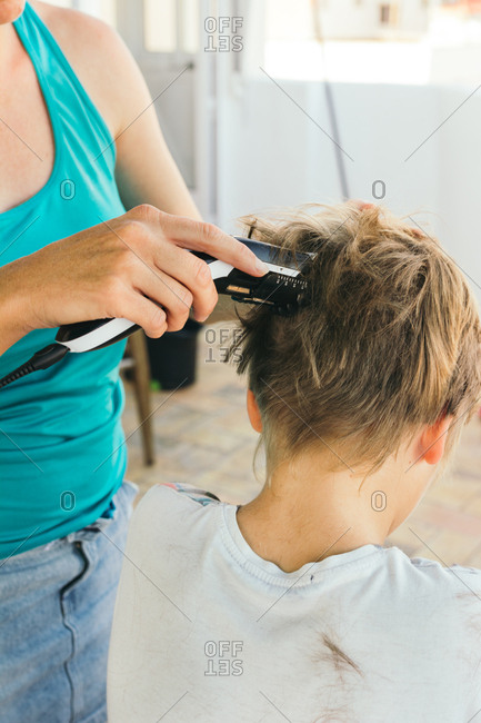 Mother cutting her son's hair, with electric cutting machine, on the terrace of the house