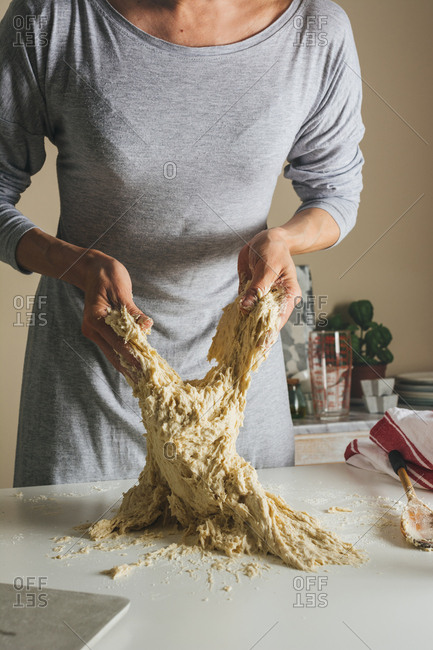 hands of woman begins to work the risen dough,