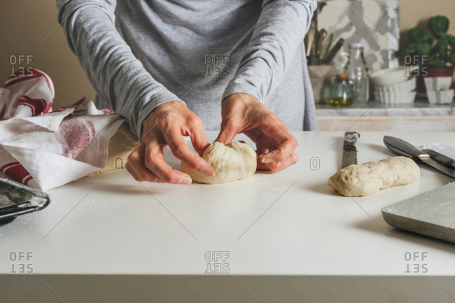 woman massing bread: folding the dough into thirds, and sealing with the fingers