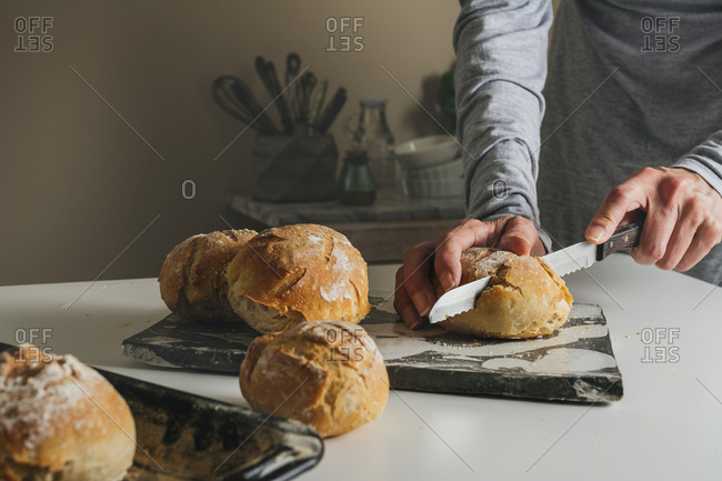Woman cutting freshly baked bread on marble table