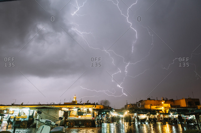 Marrakech, Morocco - April 21, 2014: Lightning in dark sky during stormy weather above illuminated city after rain