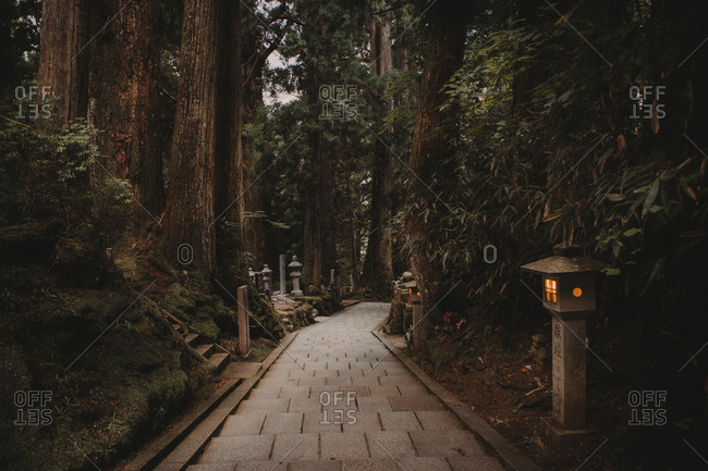 Koyasan, Japan - September 10, 2017: View of walkway running way among trees on territory of ancient oriental sacred temple