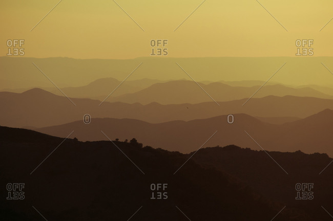 View to gradient dark hills in yellow sunlight