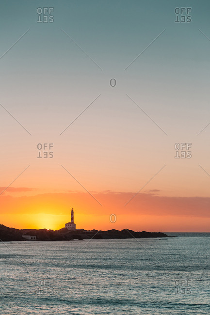 Landscape of calm sea water and rocky shoreline with silhouette of lighthouse in sunset light