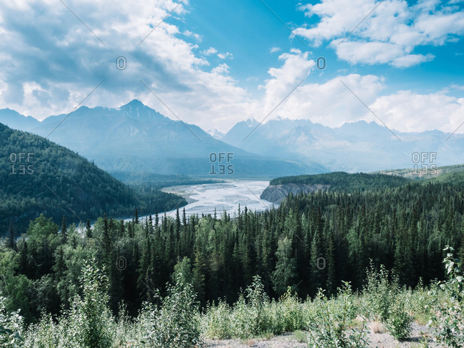 Picturesque panoramic view of river flowing in valley between mountains with woods