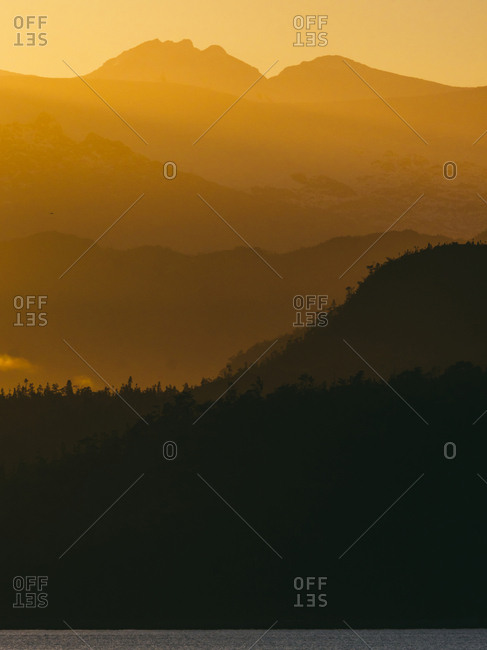 Landscape of mountain range in shades and rays of calm sunset light