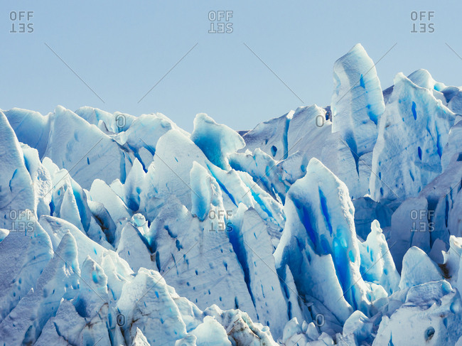 Background of blue and white sharp pieces of frozen ice in sunlight