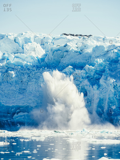 View of white glacier in sunlight and snowy splashes above water