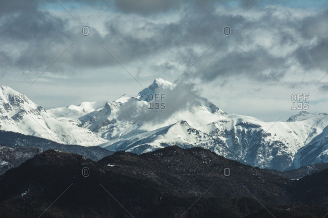 Breathtaking panorama of mountains range covered with snow under cloudy sky