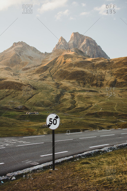 Speed sign at asphalt road placed in sunny mountains