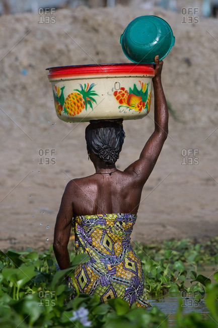BENIN, AFRICA - AUGUST 30, 2017: Back view of African woman in pond holding big bowl on head