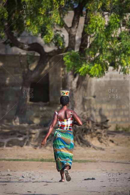 BENIN, AFRICA - AUGUST 31, 2017: Woman with bowl on head