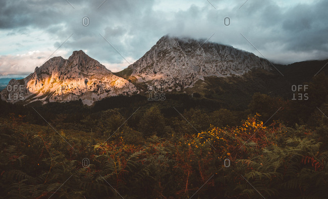 Wonderful view of terrain with woods and rocky mountains range under clouds with sun rays penetrating sky
