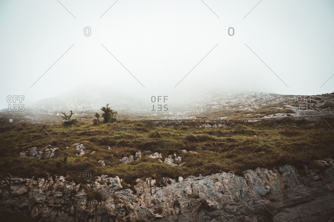 Mystic landscape of rocky terrain with green field in thick fog