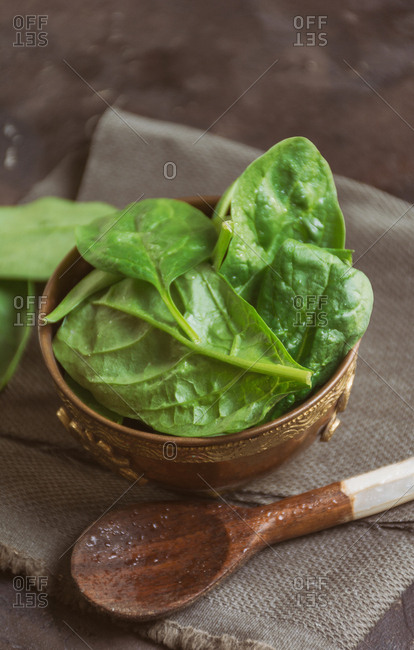 Wooden dish filled with fresh spinach leaves and behind find pears, lemons and Kiwi