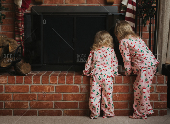 Two girls at fireplace at Christmas