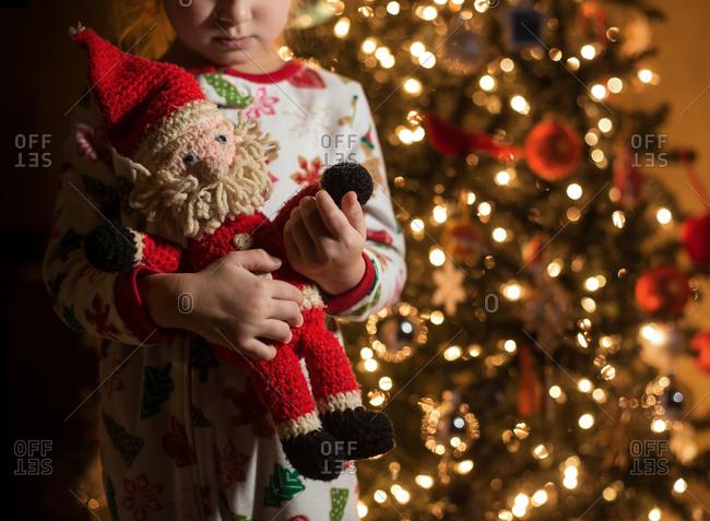 Girl holds Santa doll next to a Christmas tree