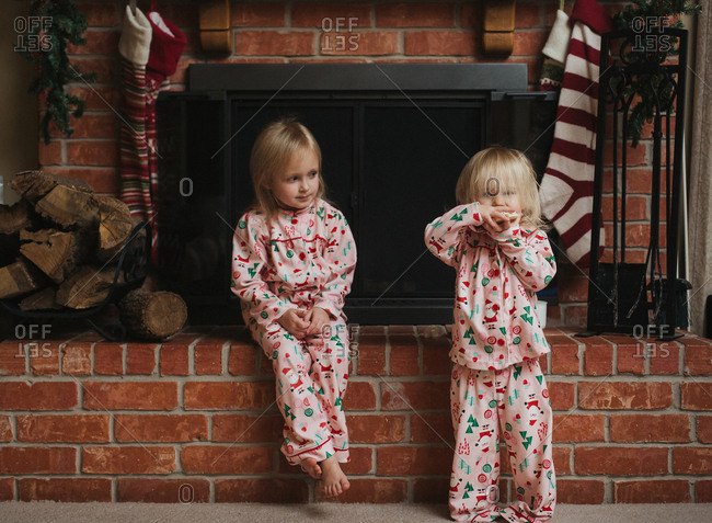 Girl eats a holiday cookie at the fireplace