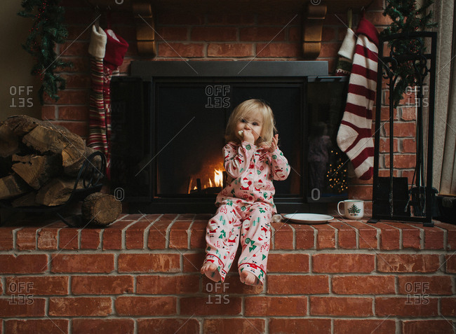 Toddler girl eating cookie at fireplace