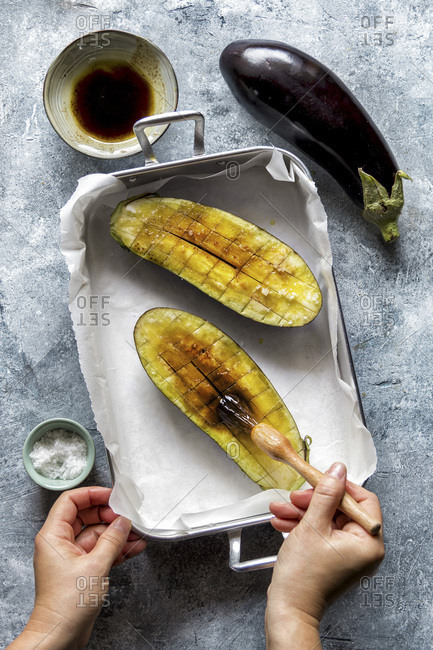 Hands brushing eggplants with olive oil. Preparing eggplant for roasting