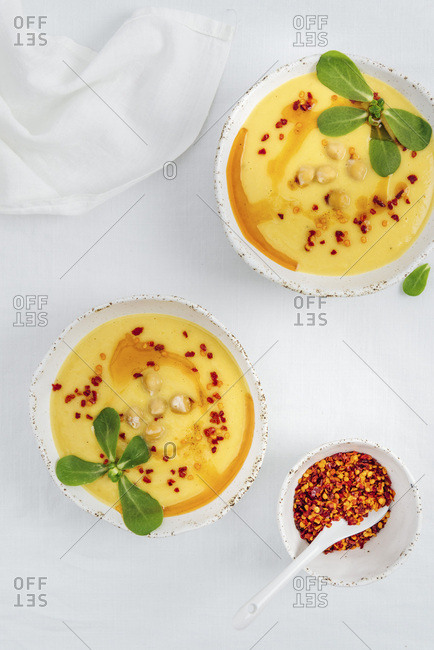 Two bowls of vegan pumpkin soup drizzled with olive oil sauce and garnished with purslane leaves and chickpeas photographed on a white background from top view. A small bowl of red pepper flakes accompanies.