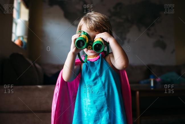Toddler girl playing dress up and looking through green binoculars