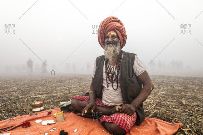 Allahlabad, India - January 28, 2013: A man sits on a blanket while applying face paint during the Maha Kumbh Mela pilgrimage, others can be seen moving in the fog behind him