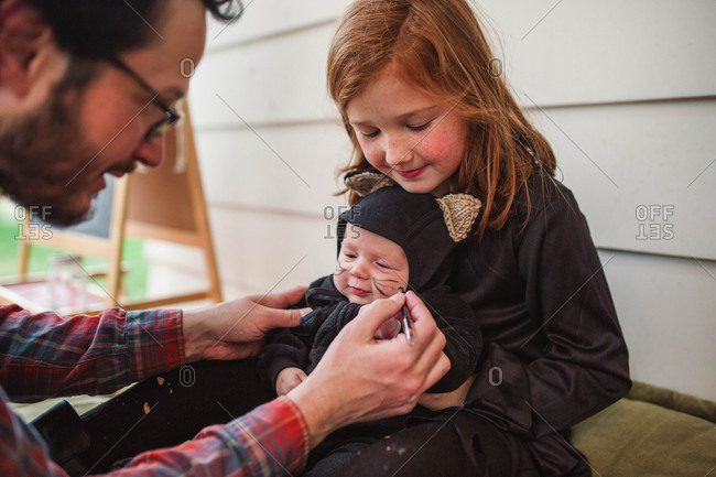 Father drawing whiskers on baby\'s face for Halloween costume