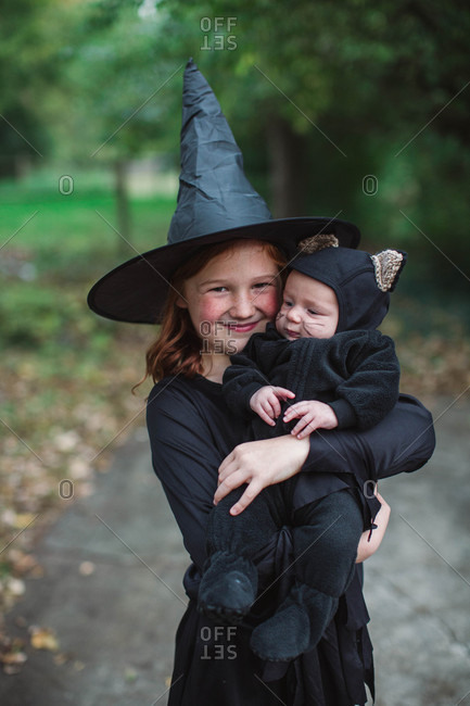 Girl dressed up as a witch for Halloween holding baby dressed up as a black cat