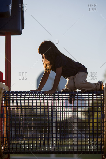 Girl crawling on top of playground equipment