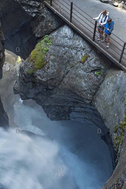 August 4, 2013: Tourist admiring Trummelbach ice waterfall formed by melting waters of glaciers Eiger, Monch and Jungfrau, Lauterbrunnen Valley, Canton Bern, Switzerland