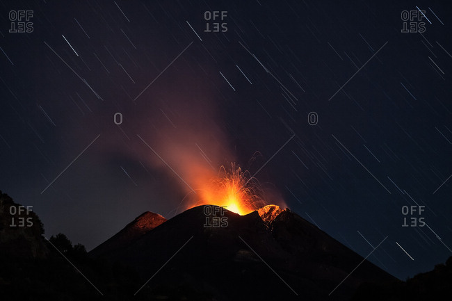A weak strombolian activity at the Southeast Crater is perfect to make a long exposure to show the movement of stars, Zafferana, Sicily, Italy