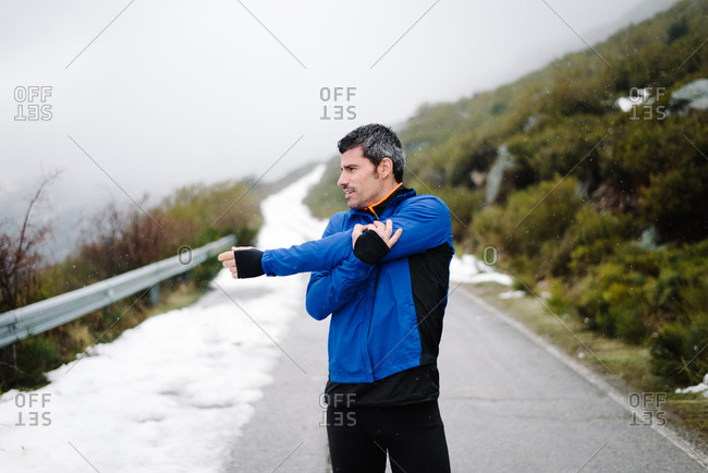 Runner training under snow on a mountain road in winter.